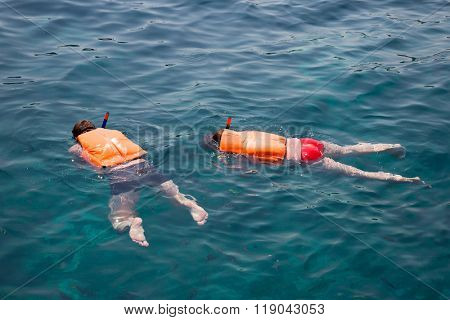People engaged in snorkeling in life jackets. Phi Phi Islands, Andaman Sea, Thailand