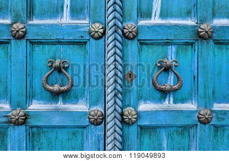Ancient Wooden Bright Turquoise Door With Aged Metal Door Handles And Rivets. Architectural Backgrou