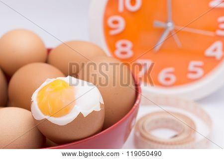 Medium-boiled Eggs  In Red Bowl With Clock For Morning Time Concept