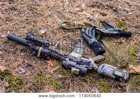 Tactical Semi Automatic Rifle And Gloves On Ground In The Forest
