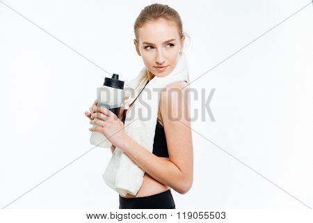 Attractive young woman athlete holding bottle of water and white towel over white background
