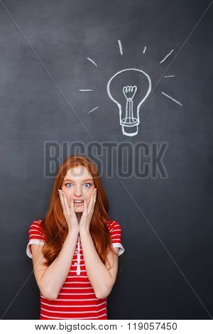 Amazed beautiful redhead young woman with hands on cheeks standing over chalkboard background with drawn electric bulb