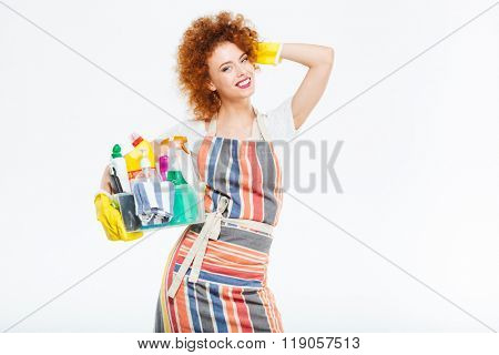 Happy beautiful curly young woman in striped apron and yellow gloves standing and holding box with cleansers over white background