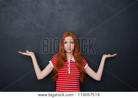 Confused pretty young woman with long red hair holding copyspace on both palms over chalkboard background