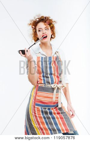 Attractive redhead young housewife with curlers in kitchen apron standing and holding soup ladle over white background