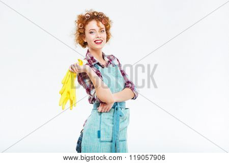 Cheerful beautiful young housewife with red curly hair in blue apron holding yellow rubber gloves over white background