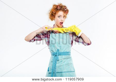 Attractive playful young housewife with red curly hair posing with yellow protective gloves over white background