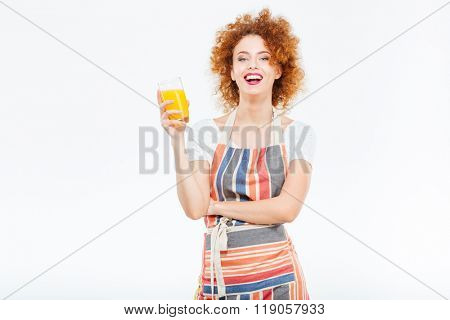Cheeful beautiful young woman in striped apron laughing and holding glass of orange juice over white background