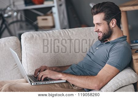 Typing new blog post. Side view of handsome young man using his laptop with smile while sitting on the couch at home