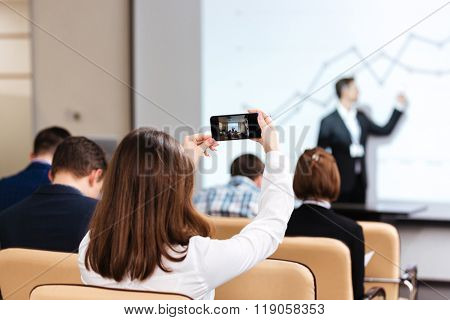 Back view of young businesswoman making video with mobile phone on business conference in boardroom