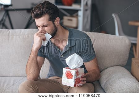 Terrible allergy. Frustrated handsome young man sneezing and using tissue while sitting on the couch at home