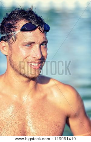 Athlete swimmer in swimming pool with swim goggles. Handsome young professional male sports adult portrait looking happy after cardio workout exercising in outdoor water, topless wearing swimwear.