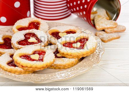 Shortbread cookies in the shape of heart with strawberry jam on wooden table.