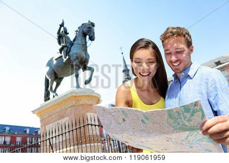 Europe travel couple looking at map in Madrid. Two happy beautiful young adults looking for directions during european summer vacations in Plaza Mayor, Madrid, Spain.