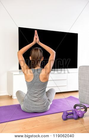 Yoga girl doing meditation exercise in living room at home. Woman watching fitness dvd workouts or streaming online videos on smart tv with flat screen television doing a training program.