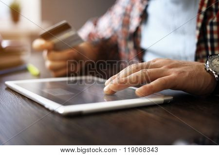 Man holding tablet pc and credit card indoor