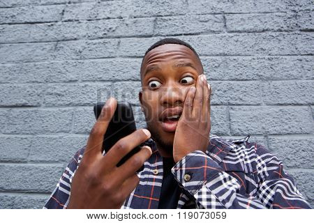 Young African Man Reading Bad Message On His Mobile Phone