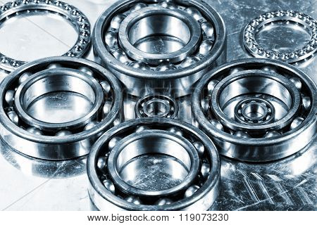 Ball bearings, titanium and steel aerospace parts in a metal blue toning concept