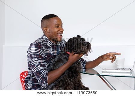 Young African Man Showing Something On Laptop To His Pet Dog
