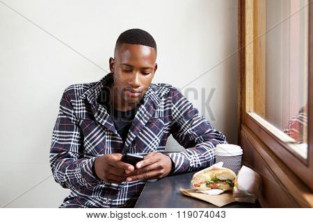 Young African Man Using Mobile Phone At A Cafe