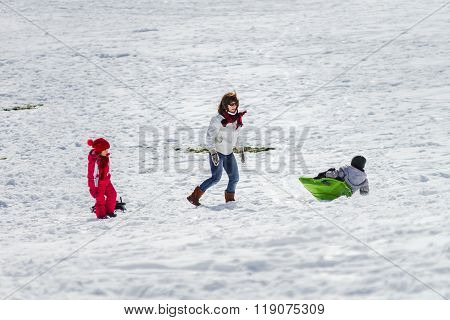 Mother With Children Sledding On Snow Hill