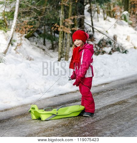 Little Girl With Snow Sleds