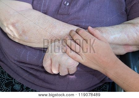 Old And Young. Child's Hand On Arm Of A Mature Woman
