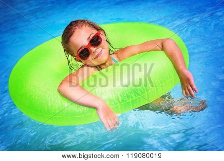 Portrait of cute happy little girl having fun in swimming pool, floating in blue refreshing water with big green rubber ring, active summer vacation on the beach
