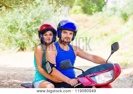 Young couple on a motor scooter ready to hit the road.