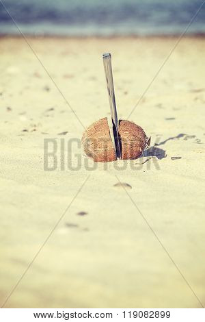 Vintage Toned Coconut Cut In Half With Knife On A Beach