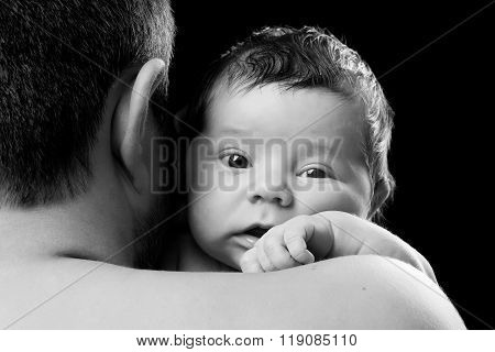 Close-up portrait of a newborn baby in dad's shoulder. Father holding child on a black background
