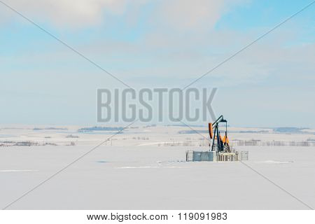 Lone Pumpjack In Snowy Field
