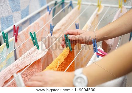 midsection of woman hands hanging up laundry