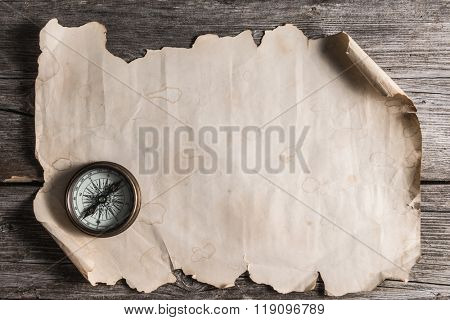 old ancient  manuscript and compass on the wooden board