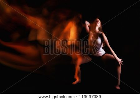 beautiful ballet dancer posing on black studio background