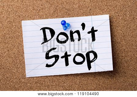 Don't Stop - Teared Note Paper Pinned On Bulletin Board