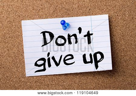 Don't Give Up - Teared Note Paper Pinned On Bulletin Board
