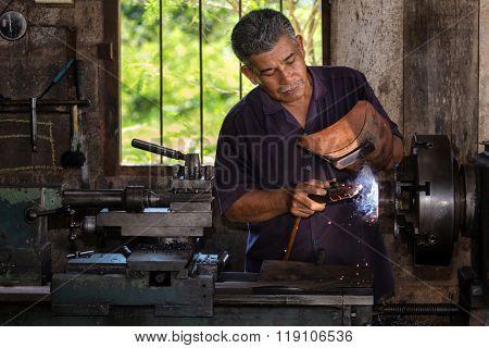 Thai worker welding a metal part in his workshop
