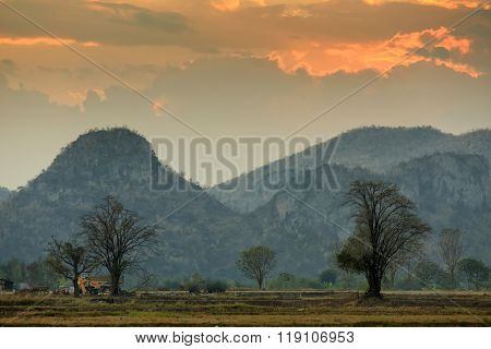 Kanchanaburi rural landscape at dusk with rice field, trees and mountains, Thailand