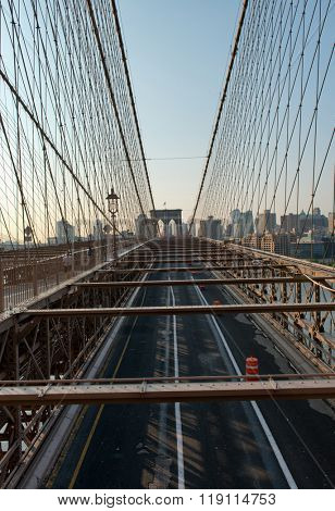 Overview of Deserted Traffic Lanes Through Girders and Cables Looking Toward Arches of Historic Brooklyn Bridge with City Skyline in Background, New York City, New York, USA at Sunrise or Sunset