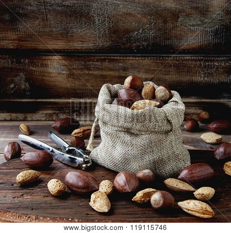 canvas bag with nuts in the shell on a wooden table with tongs for cracking nuts