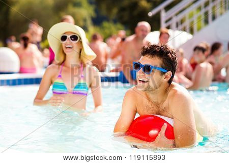 Couple with sunglasses in swimming pool. Summer and water.