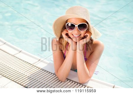 Woman with sunglasses and hat in swimming pool, water