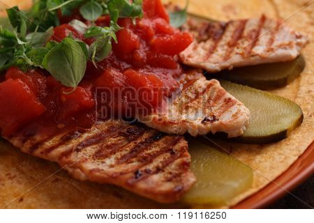 Grilled chicken meat with pickled cucumbers, tomato, and marjoram on a flatbread