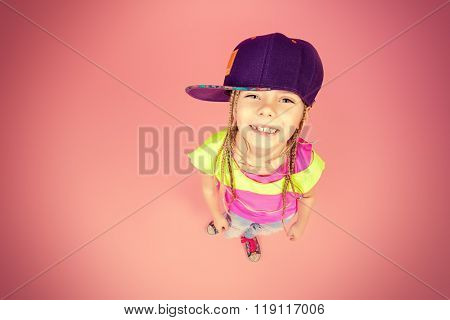 Cute little girl in a cap smiling to camera. Kid's fashion. Happy childhood.
