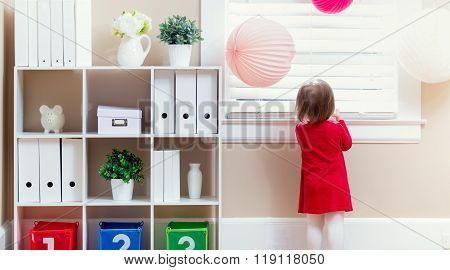 Toddler Girl Peeking Out The Window