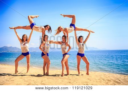 Cheerleaders Perform Swedish Falls On Beach Against Azure Sea