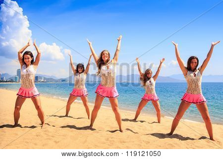 Cheerleaders Dance On Beach With Hands Upwards Against Azure Sea