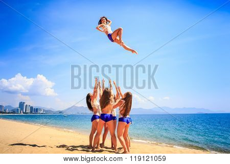 Cheerleaders Performs Stunt Basket Toss On Beach Against Resort
