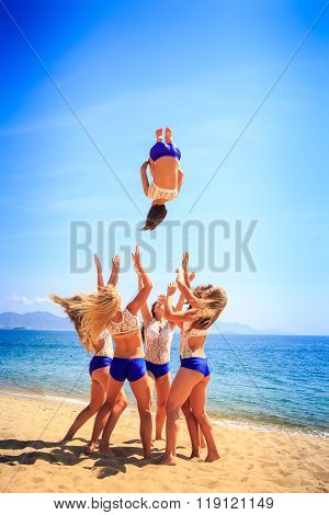 Cheerleaders In White Blue Perform Back Tuck Basket Toss On Beach